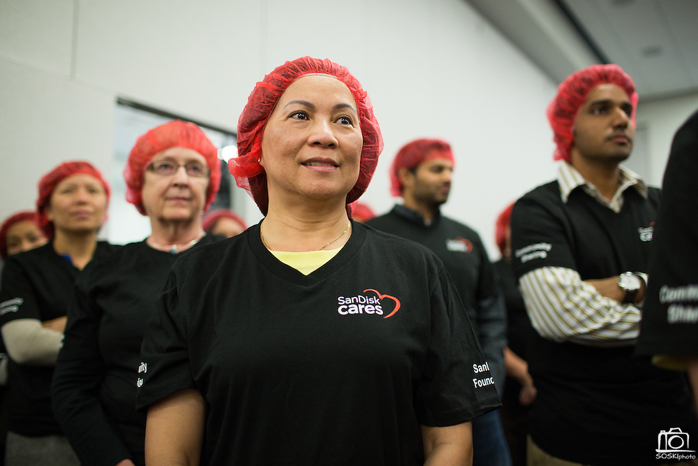 """SanDisk employee Tracy Nguyen listens to food packing instructions during the Stop Hunger Now Foundation's """"Mayday, Mayday"""" food-packing event at SanDisk Corporation in Milpitas, California, on May 13, 2014. (Stan Olszewski/SOSKIphoto)"""
