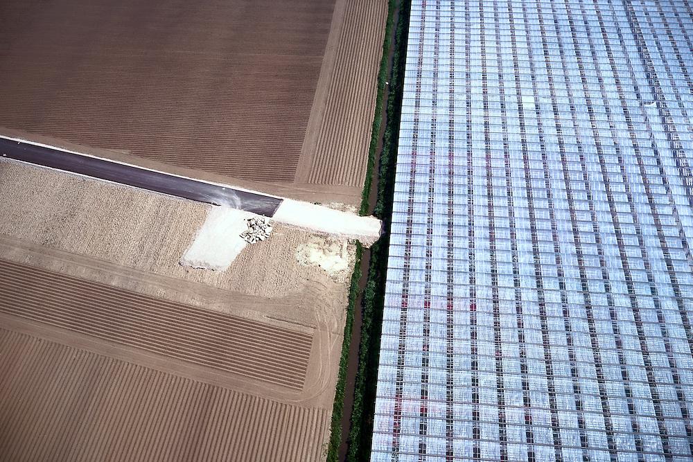 Nederland, Bleiswijk, Oosteindsche Polder, 17/05/2002; de HSL doorsnijdt het glastuinbouwgebied en grote kassen complexen moeten worden gesloopt; de werkweg voor de HSL (links) is in aanleg: tijdelijke akkers (met asperges) waar eerst kassen stonden, ook de kassen rechts zullen er aan moeten geloven; verkeer en vervoer, infrastructuur, bouwen, spoor, rail, TGV planologie ruimtelijke ordening, landschap;<br /> luchtfoto (toeslag), aerial photo (additional fee)<br /> foto /photo Siebe Swart
