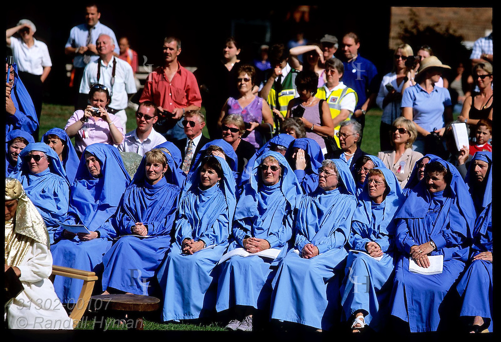 Blue-robed, mid-ranking bards sit at Gorsedd of Bards coronation during National Eisteddfod festival; Welshpool, Wales.