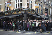 Drinkers spill out onto the street outside The Dog and Duck pub in Soho, London, England