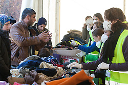 Licensed to London News Pictures. 03/11/2015. Sentilj, Slovenia. Volunteers are giving clothes to migrants at the refugee camp in Sentilj, Slovenia at the Slovenian - Austrian border . Photo: Marko Vanovsek/LNP