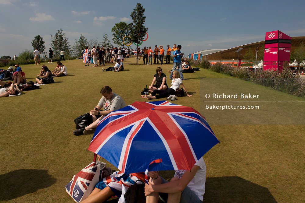 Brits enjoy a hot summer to watch live coverage from a large tv screen in the Olympic Park during the London 2012 Olympics. Under union jack umbrellas they sit on green grass located on a hilltop where giant Olympic rings act as a backdrop to spectators' family photos.  This land was transformed to become a 2.5 Sq Km sporting complex, once industrial businesses and now the venue of eight venues including the main arena, Aquatics Centre and Velodrome plus the athletes' Olympic Village. After the Olympics, the park is to be known as Queen Elizabeth Olympic Park.