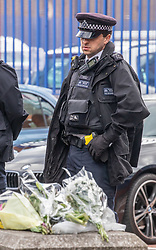 © Licensed to London News Pictures. 25/09/2020. London, UK. Police officers guard flowers outside Croydon Police Station in South London where a custody sergeant was shot dead inside the station last night. The Shooter who turned the gun on himself has survived and was taken to hospital in critical condition. Photo credit: Alex Lentati/LNP