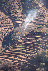 4 January 2018, Atlas Mountains, Morocco: Berbers are believed to have inhabited the Maghreb region in North Africa for more than 12,000 years. Here in the village of Imi Oughlad in Morocco, smoke rises from burning leaves as farmers prepare the land to grow barley.