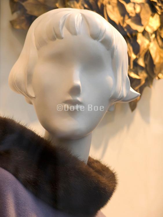 a faceless mannequin wearing a fur collar