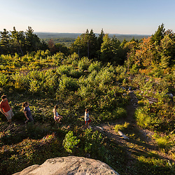 A family of four hiking on the summit of Mount Agamenticus in York, Maine.