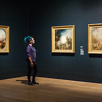 London, UK - 8 September 2014: a gallery assistant poses next to 'War: The Exile and Rock Limpet exhibited 1842' (L) and other works from the 1840s by J.M.W. Turner