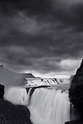 The Gullfoss (Golden Falls) Waterfall in Iceland under a dark sky.