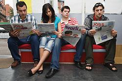 Group of Eastern European people looking for work through newspapers,