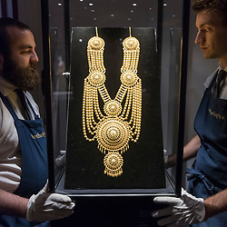 "© Licensed to London News Pictures. 25/10/2019. LONDON, UK. Technicians present ""A garland-type gold necklace, probably South India"" (Est. GBP20-30k).  Preview of ""GOLD: The Midas Touch"" at Sotheby's in New Bond Street.  Artworks spanning six centuries dedicated to gold will be offered for sale on 29 October.  Photo credit: Stephen Chung/LNP"