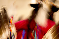 A swish of color provided by the blur of a pow wow dancer with feathers and a rich red shirt and a top hat taken from behind.