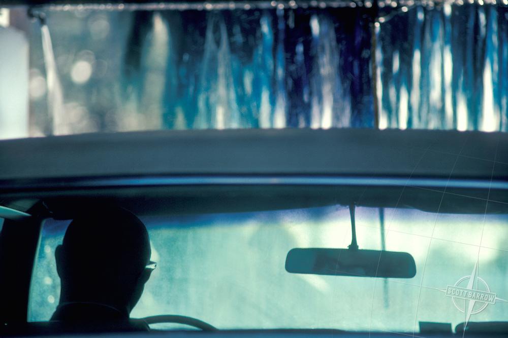 Man waiting in car at carwash.
