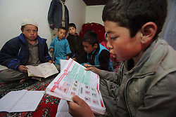 Boys complete their homework by the light from micro hydro powered generator.  NCA supported the construction of this system. Dara-e-Foladi Village,, Bamyan Province, Afghanistan