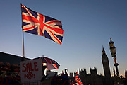 British union jack flags on a tourist trinket stall are in the foreground with Big Ben and the Houses of Parliament in the distance, on 29th November 2016, in London, England.