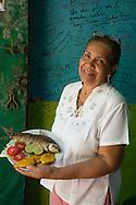 "Mary Gandilara de Barrera, owner of Comedor Costeño restaurant, with a dish of ""bocachico frito"""