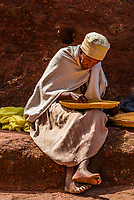Ethiopian Orthodox nuns cleaning wheat, Bete Maryam (St. Mary's Church), one of 11 rock hewn churches in Lalibela, Ethiopia.