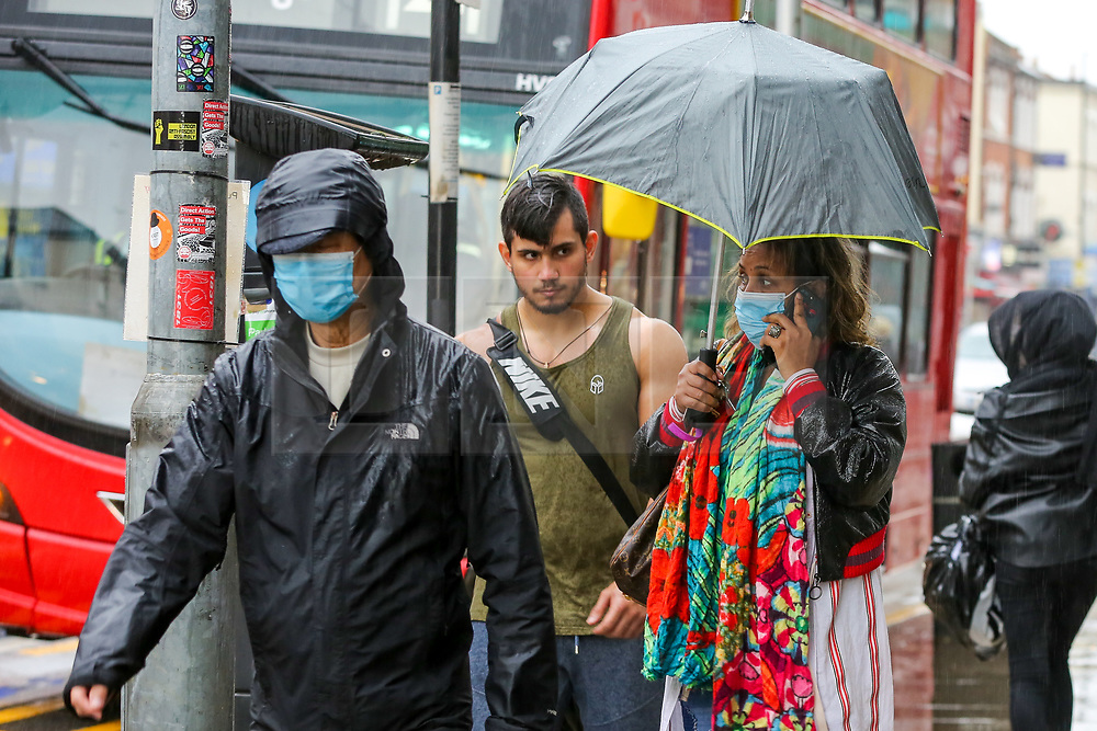 © Licensed to London News Pictures. 09/10/2020. London, UK. A woman wearing a face covering shelters from the rain underneath an umbrella in north London. According to the Met Office more rain is forecast for the weekend. . Photo credit: Dinendra Haria/LNP