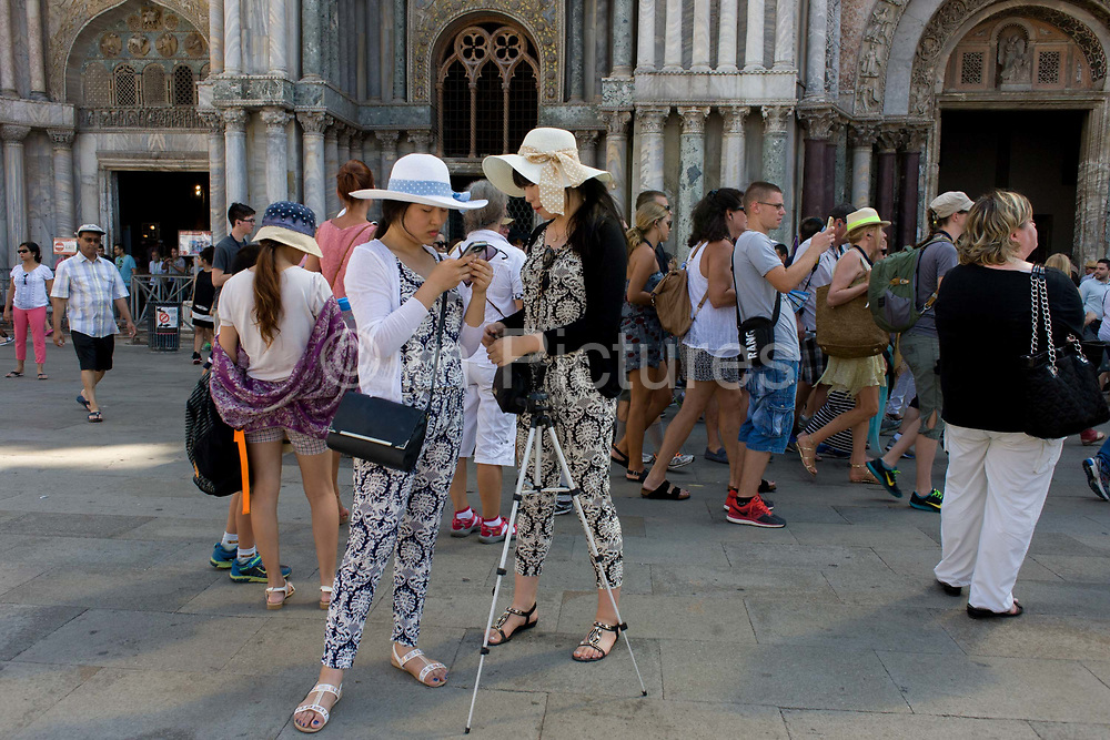 Girl tourists in similar clothing outside Basillica di San Marco in Piazza San Marco, Venice, Italy. The wide expanse of Piazza San Marco is in the heart of Venice and where, for most daylight hours, the pavement is crowded with humanity as the influx of tourists who, in their own way, flood the narrow streets with sun-shading umbrellas and the smaller canals with gondolas. Venice attracts 22-million visitors each year (for a city of only about 60,000 residents) while the cultural protection organisation, Italian Nostra, warns that Venice can only accommodate about 33,000 visitors per day but currently at least 60,000 daily.