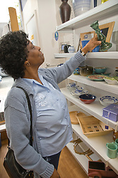 woman looking at bric a brac on shelves in Charity shop,