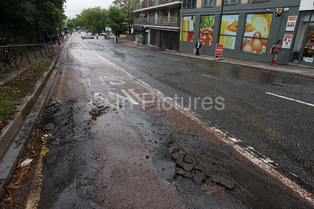 An empty road due to a cracked road surface of tarmac, weeks after disastrous flooding in nearby Herne Hill, south London. Denmark Hill has been closed in both directions due to another burst water main in multiple locations across the road (A215) between the junctions of Champion Hill and Champion Park in south London. Water is seen running towards Kings College Hospital, 200m downhill and Denmark Hill is a major thoroughfare for the hospital's Accident & Amergency (A&E) department and used by ambulances and emergency traffic throughout the day and night.