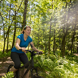 A woman rides her mountain bike at the Shepards Farms Preserve in Norway, Maine.