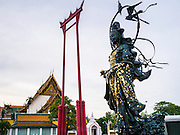"""12 NOVEMBER 2012 - BANGKOK, THAILAND:   The Giant Swing (Sao Ching Cha) formerly used in Brahmin rites, (center) with Wat Suthat in the background and a temporary Chinese shrine in the foreground along   Bamrung Muang Street in Bangkok. Thanon Bamrung Muang (Thanon is Thai for Road or Street) is Bangkok's """"Street of Many Buddhas."""" Like many ancient cities, Bangkok was once a city of artisan's neighborhoods and Bamrung Muang Road, near Bangkok's present day city hall, was once the street where all the country's Buddha statues were made. Now they made in factories on the edge of Bangkok, but Bamrung Muang Road is still where the statues are sold. Once an elephant trail, it was one of the first streets paved in Bangkok. It is the largest center of Buddhist supplies in Thailand. Not just statues but also monk's robes, candles, alms bowls, and pre-configured alms baskets are for sale along both sides of the street.    PHOTO BY JACK KURTZ"""
