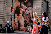 Londoners pass beneath a tall advertising billboard, by menswear retailer Suitsupply, of an intimate kissing couple on Covid Freedom Day. This date is what Prime Minister Boris Johnsons UK government has set as the end of strict Covid pandemic social distancing conditions with the end of mandatory face coverings in shops and public transport, on 19th July 2021, in London, England.