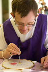 Portrait of Day Service user with learning disability concentrating on his painting,