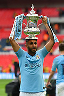 Riyad Mahrez (26) of Manchester City holds up the FA Cup at full time on his head as he celebrates during the The FA Cup Final match between Manchester City and Watford at Wembley Stadium, London, England on 18 May 2019.