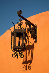 North America, Mexico, San Miguel de Allende,wrought-iron street lamp and its shadow on orange wall