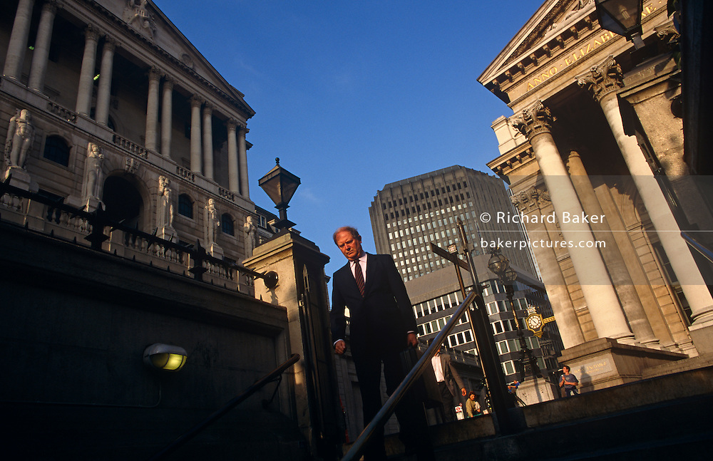 A middle-aged man dressed in a smart dark suit is about to descend underground to Bank tube (subway) station beneath the converging columns of the famous Bank of England and Cornhill Exchange at Bank Triangle in the City Of London, the financial district, otherwise known as the Square Mile. The gentleman is on his way home in the afternoon, his commuting exodus to be shared by its daily working population of 311,000. This perspective of suggests a bank and its architecture looking powerful and influential in the UK's economy. The pillars give a sense of establishment, a scene of classic stability and strength.