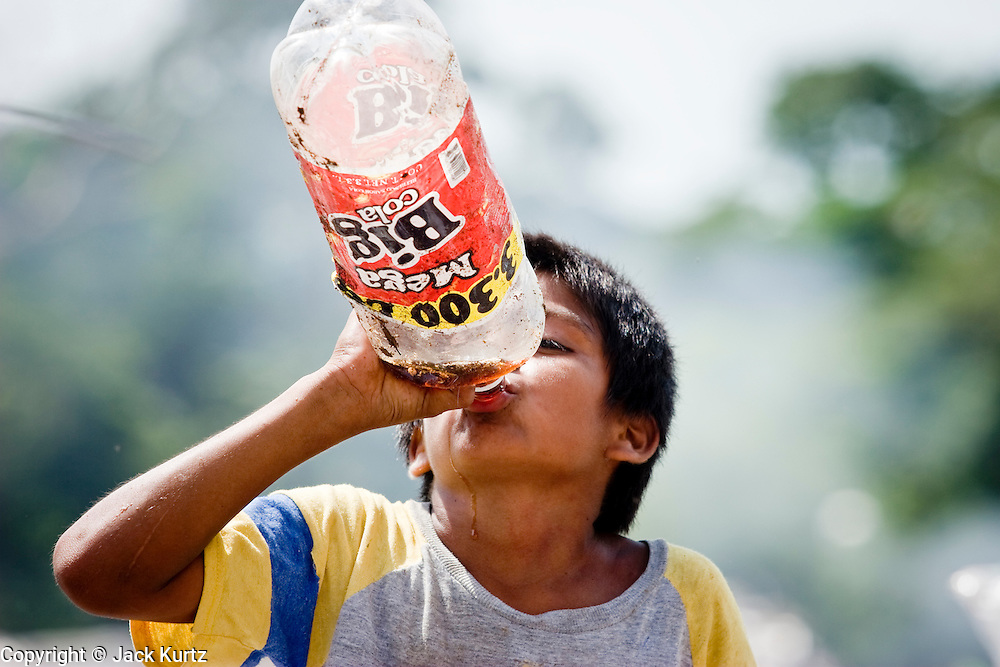 09 NOVEMBER 2004 - TAPACHULA, CHIAPAS, MEXICO: Carlos Lopez Perez, 12, finishes a bottle of nearly empty soda he found while working in the municipal garbage dump in Tapachula, Chiapas, Mexico. About 130 people, the poorest of the poor in Tapachula, work in the dump picking through the garbage hoping to find tidbits they can use or sell to brokers who sit on the edge of the dump and resell the garbage. Most of the dump workers are Guatemalan migrants who crossed the border hoping, at one time, to get to the United States. Now they have settled for an existence on the very edge of Mexican society. PHOTO BY JACK KURTZ