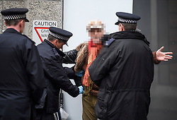 **UNPIXELATED VERION AVAILABLE ON REQUEST**<br /> © Licensed to London News Pictures. 08/04/2018. London, UK. A man being searched, before being arrested by police after being found carrying what appears to be a weapon at an anti-semitism demonstration outside the headquarters of the Labour Party, in London. Labour party leader Jeremy Corbyn recently apologised for what he described as 'pockets' of anti-Semitism within Labour Party. Photo credit: Ben Cawthra/LNP