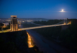 """© Licensed to London News Pictures; 27/05/2021; Bristol, UK. A full Moon is seen over the Clifton Suspension Bridge on it's way to setting. The full Moon in May is known as the """"Flower Moon"""" and this full Moon is also a supermoon, the largest full Moon of 2021. Being only 357,462km away from Earth, the Moon will appear 30 per cent brighter and 14 per cent larger than some previous full Moons. Photo credit: Simon Chapman/LNP."""