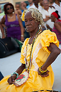 Female Cuban older elderly woman posing for a portrait wearing colourful costume, performance in Havana old town, local dance and theatre group enacting the slave trade, colonial rule and how African religion and beliefs continuing, becoming what is now Santeria.