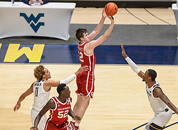 Feb 13, 2021; Morgantown, West Virginia, USA; Oklahoma Sooners guard Austin Reaves (12) shoots a three pointer over West Virginia Mountaineers forward Gabe Osabuohien (3) during the first half at WVU Coliseum. Mandatory Credit: Ben Queen-USA TODAY Sports
