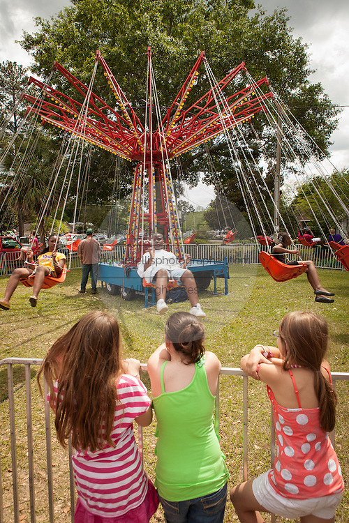 Children wait to ride an old fashion carnival swing ride at the World Grits Festival April 14, 2012 in St. George, SC. The festival celebrates the southern love for the sticky corn porridge