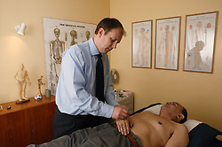 Practitioner inserting acupuncture needle in treatment room,