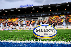 A premiership rugby match ball rests on the new artificial grass as players warm up behind before the first half of the match - Photo mandatory by-line: Rogan Thomson/JMP - Tel: Mobile: 07966 386802 16/02/2013 - SPORT - RUGBY - Allianz Park - Barnet. Saracens v Exeter Chiefs - Aviva Premiership. This is the first Premiership match at Saracens new home ground, Allianz Park, and the first time Premiership Rugby has been played on an artificial turf pitch.