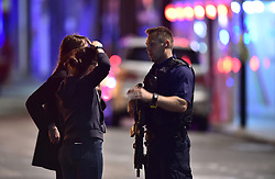 """Armed Police talk to members of the public outside London Bridge Hospital as police are dealing with a """"major incident"""" at London Bridge."""