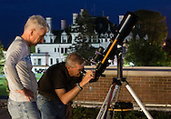 Middletown, New York - SUNY Orange professor Kevin McGee, left, watches a member of the public use a 4-inch refractor telescope during  an astronomy program on the roof  of the Rowley Center for Science and Engineering on the Middletown campus on May 12, 2015. The program was run by SUNY Orange adjunct assistant professor Tom Blon and sponsored by SUNY Orange Cultural Affairs. Morrison Hall is in the background.