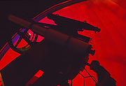 A silhouetted astronomer peers through a large telescope bathed in red light peering into space.