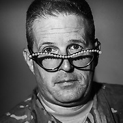 A subject sits for a portrait wearing horn rimed glasses for a project on Self-Identity.