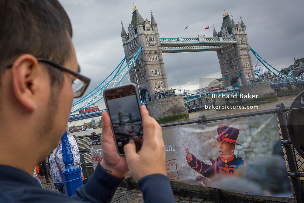 A tourist photographs Tower Bridge near the image of a Beefeater on a railing in front of the Tower of London, on 14th September 2017, in London, England.
