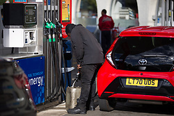 © Licensed to London News Pictures.  29/09/2021. London, UK. A man is seen filling a canister on foot as others queue  in cars for fuel at a petrol station in Lewisham, south London. The government has put army troops on standby to help distribute gasoline and help ease a fuel drought, caused by a shortage of truck drivers.  Photo credit: Marcin Nowak/LNP