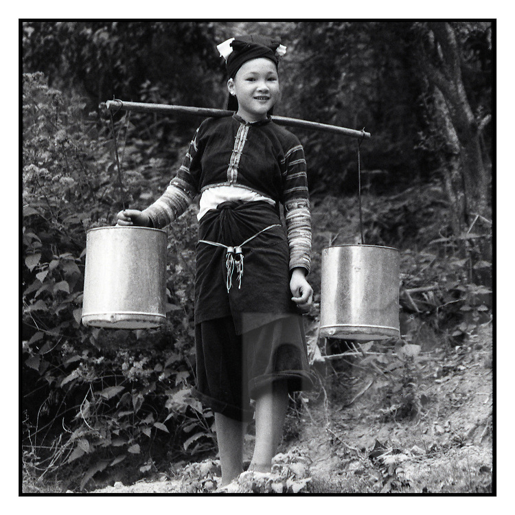 Portrait of a young ethnic girl carrying buckets of water on a yoke in Bao Lac, Cao Bang Province, Northern Vietnam, Southeast Asia