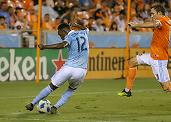 August 4, 2018 - Houston, TX, U.S. - HOUSTON, TX - AUGUST 04:  Sporting Kansas City forward Gerso (12) takes a shot on goal as Houston Dynamo forward Andrew Wenger (11) leaps in to intercept the ball during the soccer match between Sporting Kansas City and Houston Dynamo on August 4, 2018 at BBVA Compass Stadium in Houston, Texas.  (Photo by Leslie Plaza Johnson/Icon Sportswire) (Credit Image: © Leslie Plaza Johnson/Icon SMI via ZUMA Press)