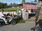 """Sept. 27, 2009 -- PATTANI, THAILAND: A Thai soldier walks past a roti (Malaysian flatbread) vendor and children going to school in Pattani. Schools and school teachers have been frequent targets of Muslim insurgents in southern Thailand and the army now provides security at many government schools.  Thailand's three southern most provinces; Yala, Pattani and Narathiwat are often called """"restive"""" and a decades long Muslim insurgency has gained traction recently. Nearly 4,000 people have been killed since 2004. The three southern provinces are under emergency control and there are more than 60,000 Thai military, police and paramilitary militia forces trying to keep the peace battling insurgents who favor car bombs and assassination.  Photo by Jack Kurtz / ZUMA Press"""