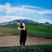 Female golf pro in sand trap .