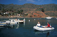 Couple in rubber zodiac raft dingy boat pulling into dock at Two Harbors, Catalina Island, California